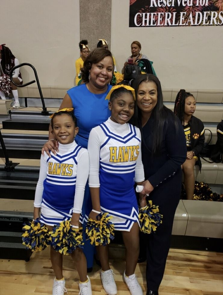principal with cheerleaders and board memner